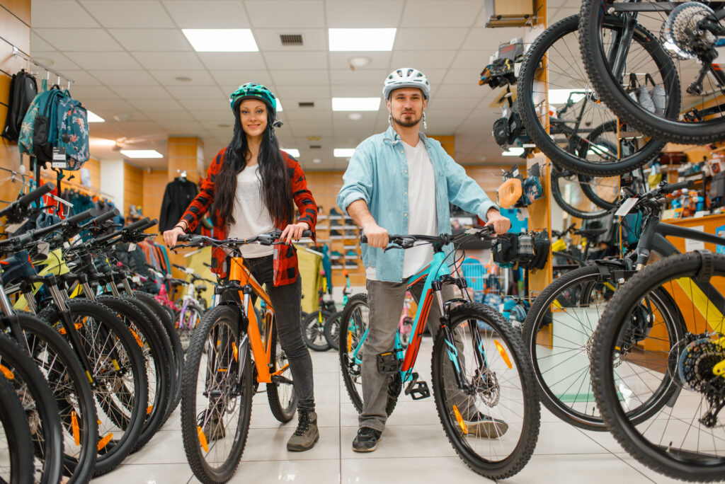 Couple in cycling helmets choosing bicycles, shopping in sport shop. Summer season extreme lifestyle, active leisure store, customers buying cycles