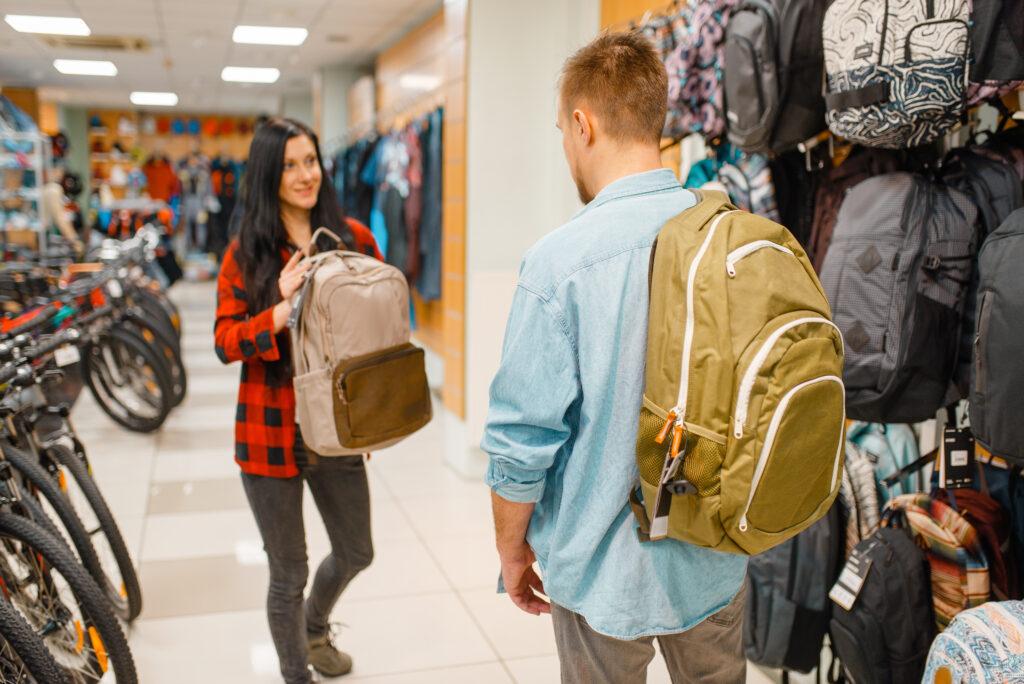 Couple choosing backpacks for travelling, shopping